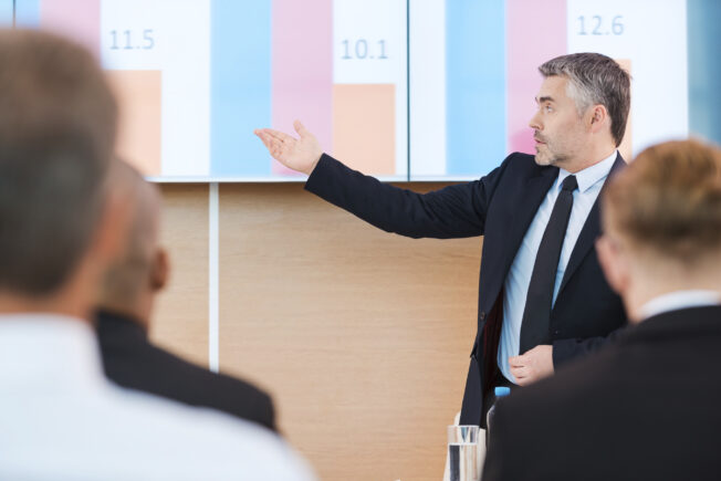 Talking about numbers. Confident mature man in formalwear pointing projection screen with graph on it while making presentation in conference hall with people on the foreground